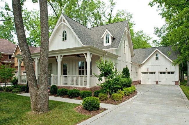Традиционный американский экстерьер дома с гаражем и мансардой Г-образной формы. Кирпичная кладка фундамента, настенный деревянный сайдинг, черепичная двускатная крыша – оформление дома и совмещенного с ним гаража