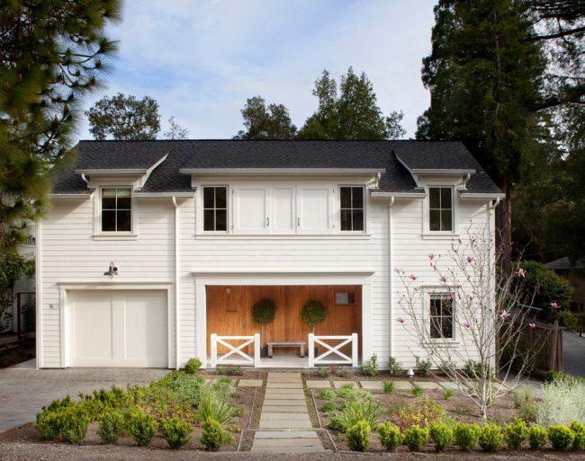 Белый двухэтажный дом, оформленный деревянным сайдингом, со встроенным гаражом