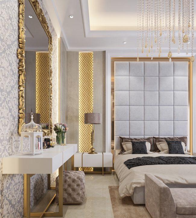 Спальня класса люкс с нотами декадентства в декоре. Высокое изголовье обито искусственной замшей, а массивная позолоченная рама зеркала перекликается с подсвеченными золотистыми вставками на стене