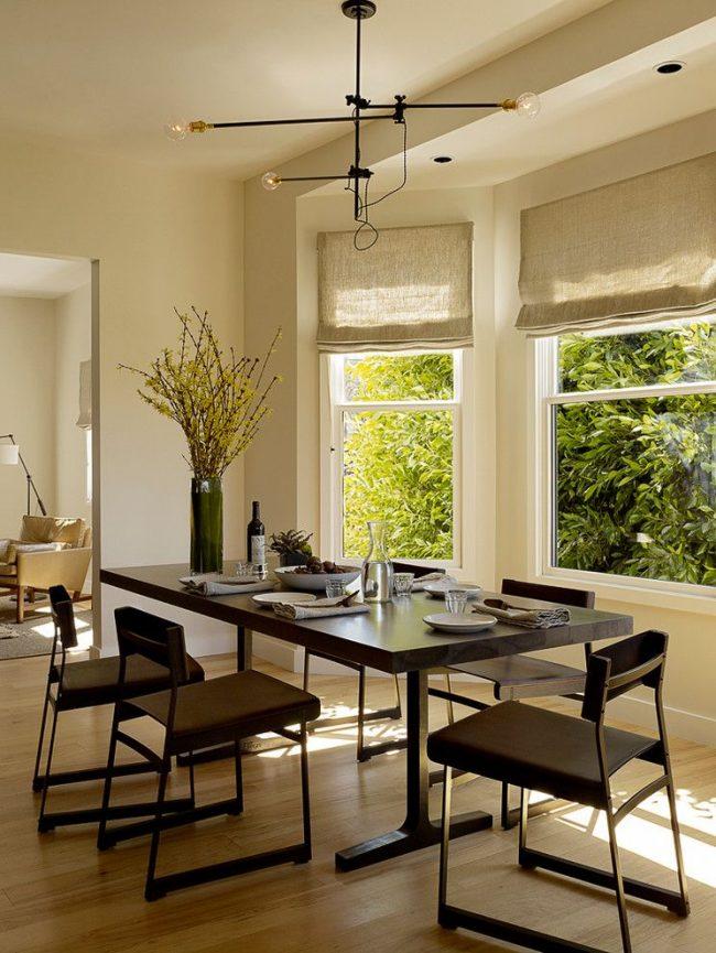 Лаконичная столовая комната с римскими шторами невысокой плотности натуральной ткани в качестве тюли, пропускающей солнечный свет