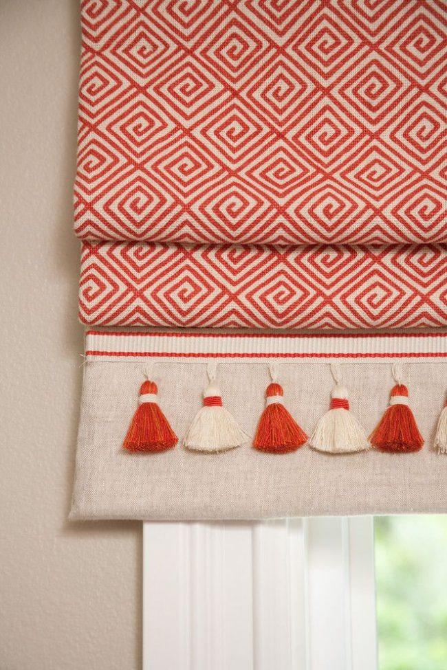 Декорированное кисточками основное полотно римских штор с белым фоном и оранжевым рисунком