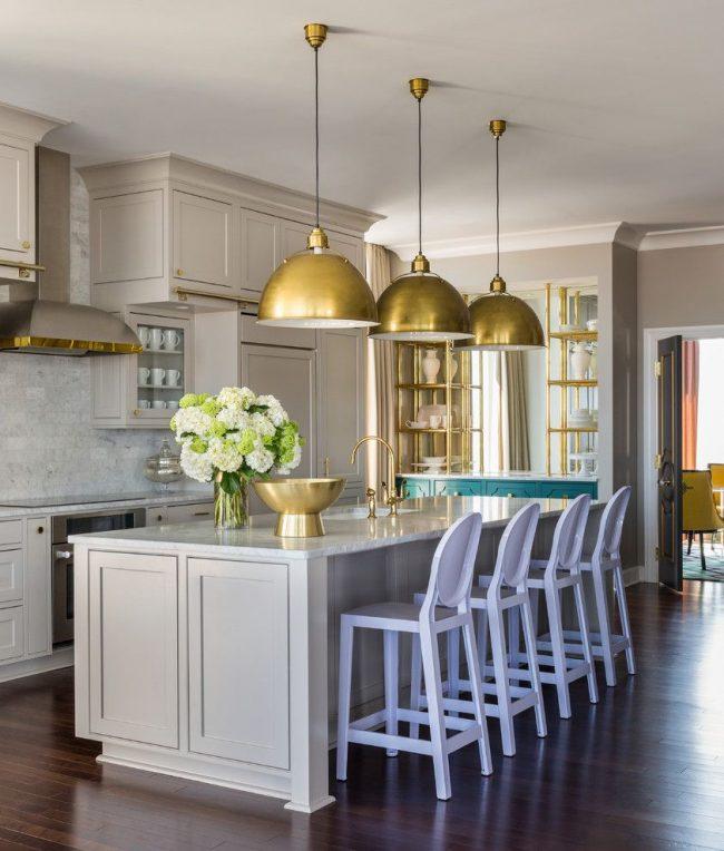 Серый цвет теплой гаммы в классическом интерьере кухни. Золотые декоративные детали: кухонная фурнитура, абажуры подвесных ламп, смеситель для кухни, открытые полки для посуды и т.д.