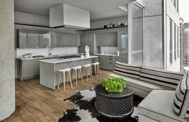 Светло-серое оформление современной кухни с белыми вкраплениями приумножает естественное освещение, исходящее из масштабного окна