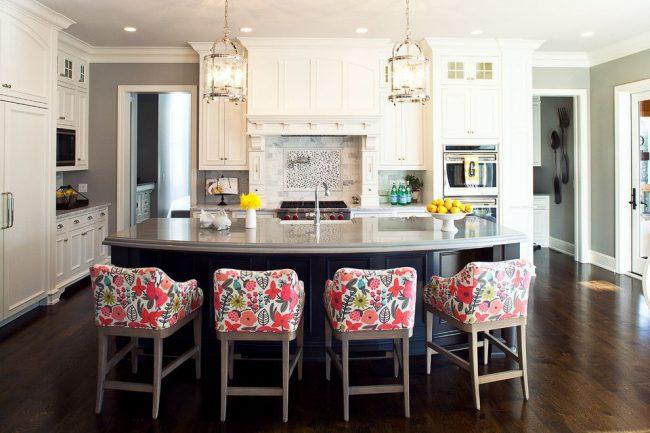 Кухонный остров из черного дерева с серой гранитной столешницей и мягкие кресла с ярким абстрактным растительным принтом – центр современной кухни серо-белого цветового оформления