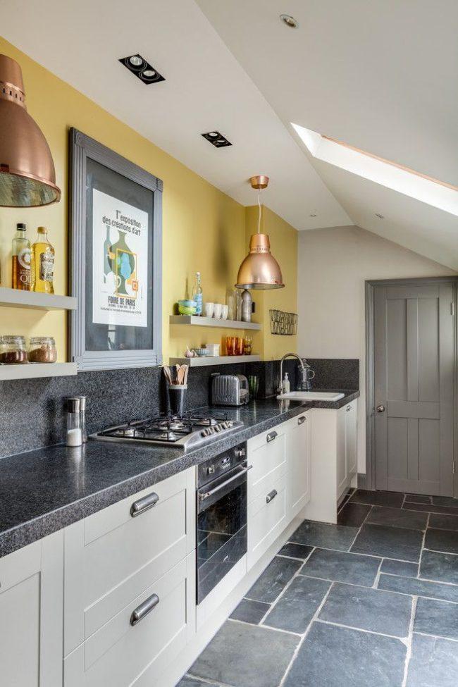 Серо-желтая кухня. Серый цвет в интерьере: кухонный фартук, столешницы, двери, бытовые приборы. Центральная стена оформлена желтым цветом. Медный цвет абажуров – дополнительный цвет, поддерживающий желтый в интерьере современной кухни