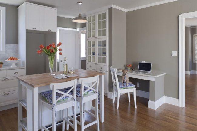 Однотонные серые стены на кухне в сочетании с белым кухонным гарнитуром. Оригинальная особенность во встроенной мебели