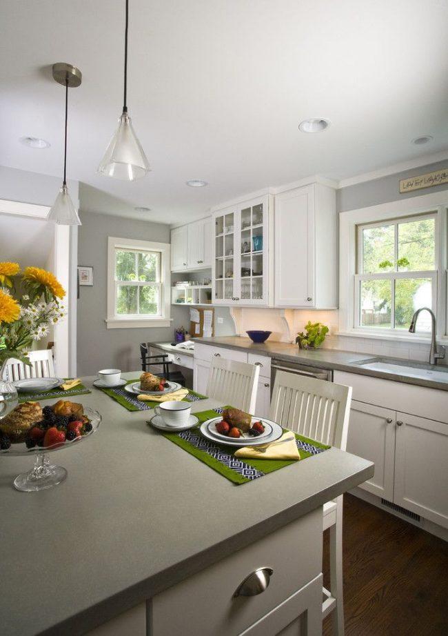 Светло-серый и белый в оформлении кухни. Темный деревянный пол и декоративные аксессуары – акценты. Плюс интерьера – визуальное увеличение пространства