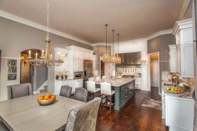 Пример серой классической кухни. Отличительные черты стиля: белые потолочные карнизы, глянцевые гранитные столешницы, кресла с текстильной принтованной обивкой, декорированные массивные люстры