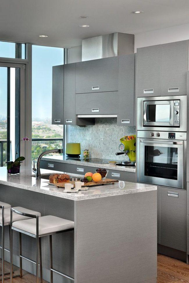 Серая лаконичная кухня известного бренда IKEA в интерьере с серой отделкой, глянцевыми металлическими духовыми шкафами и яркими акцентами в виде мелкой бытовой техники