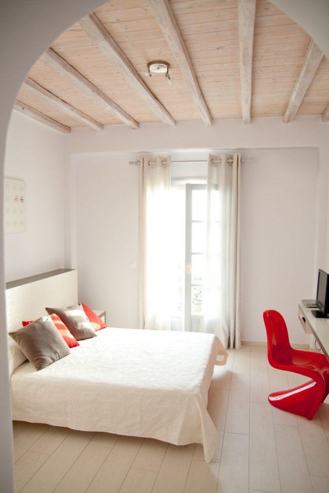 Спальня в кремовых тонах с высокими потолками и небольшими яркими акцентами
