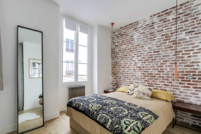 Спальня с большим зеркалом, выполненная в стиле лофт
