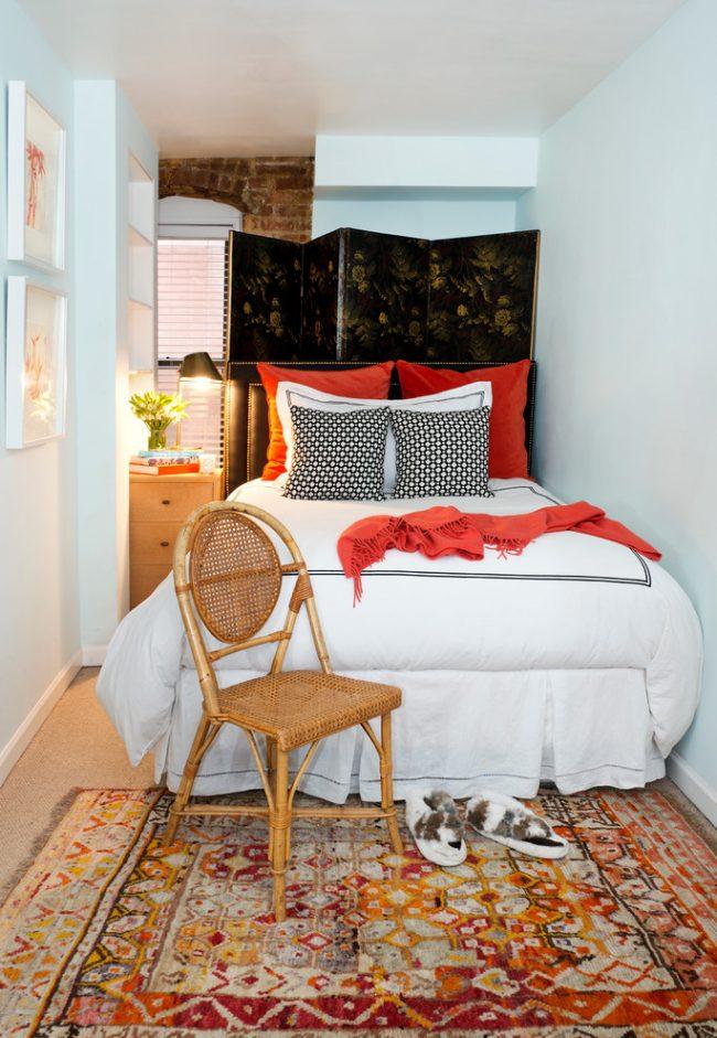 Узкая спальня с белыми стенами и уютным текстилем в теплых тонах