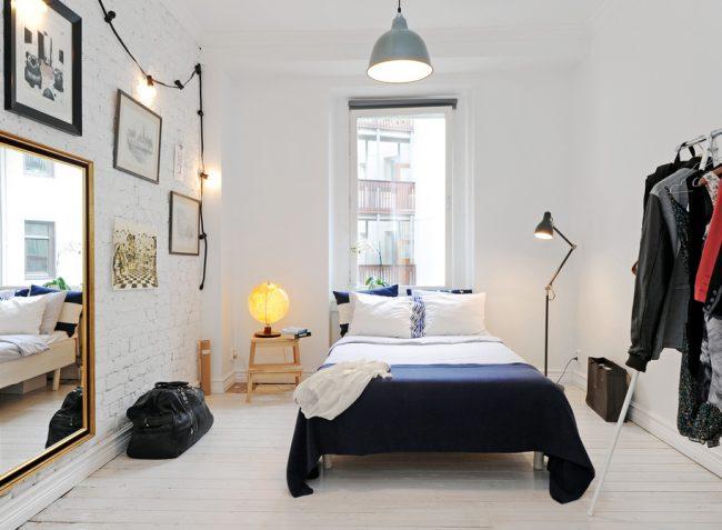 Современное оформление небольшой спальни с минимальным количеством мебели и всевозможными приемами увеличения пространства