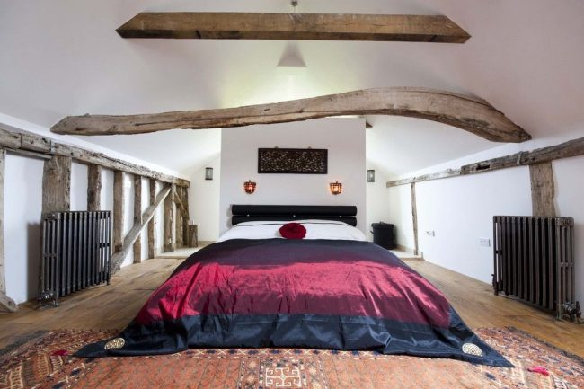 Просторная спальня с массивными чугунными батареями по бокам от кровати