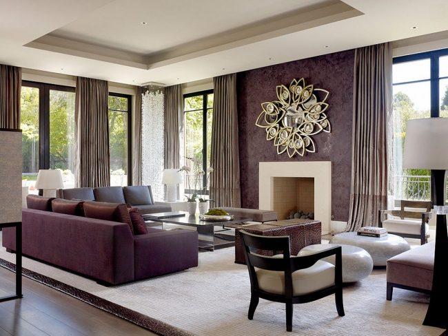 Просторная гостиная с одной акцентной стеной окрашенной фактурной краской фиолетового цвета