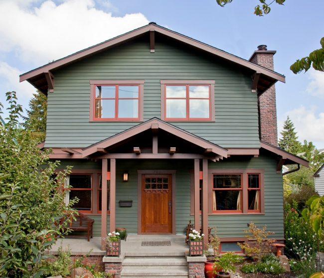 Красивое сочетание зеленого и коричневого цветов в оформлении фасада двухэтажного дома
