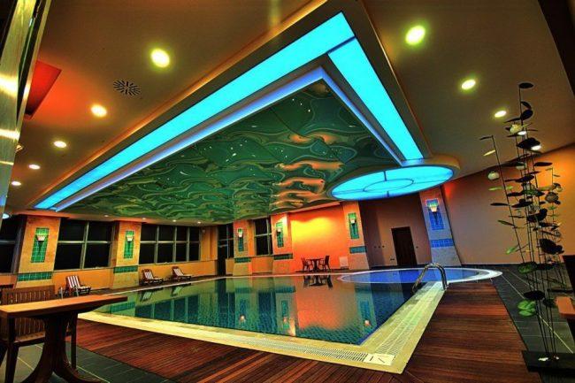 Волнистый натяжной потолок над бассейном