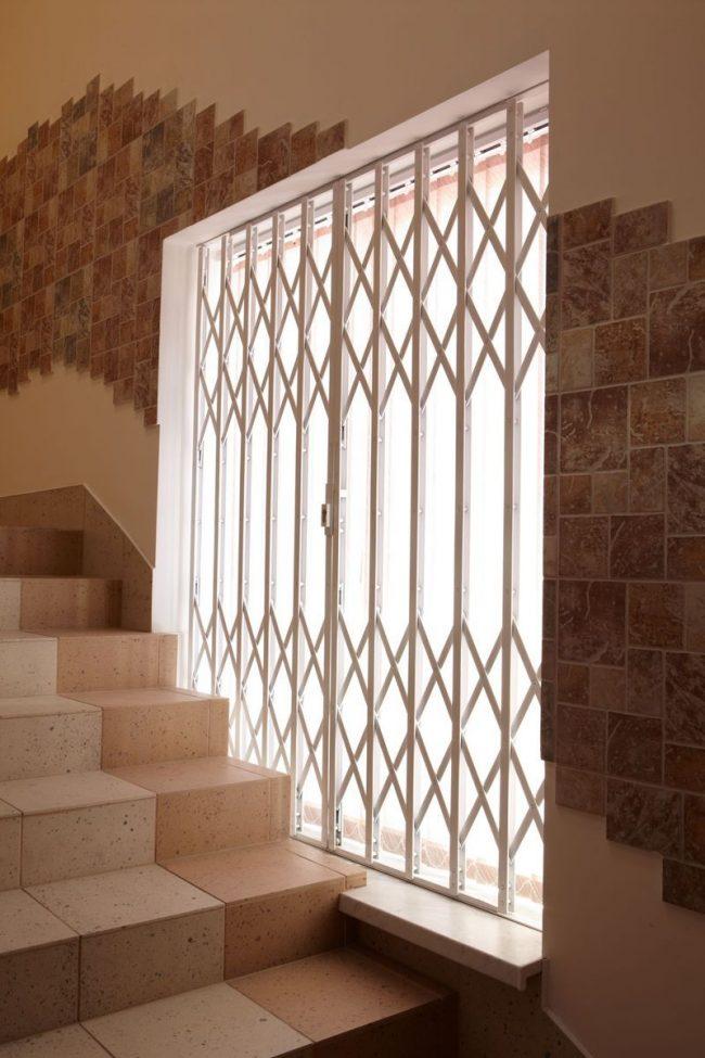 Внутренняя раздвижная металлическая решетка на окне