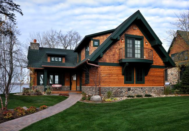 Контраст коричневого бруса и черной крыши в оформлении частного дома