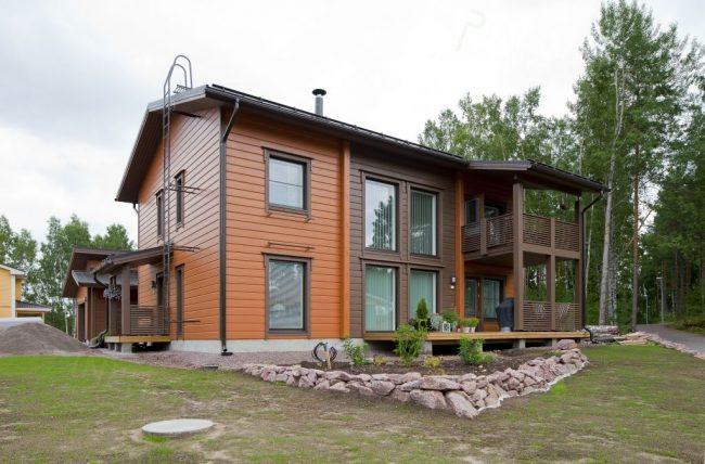 Двухэтажный частный дом из клееного бруса двух оттенков коричневого
