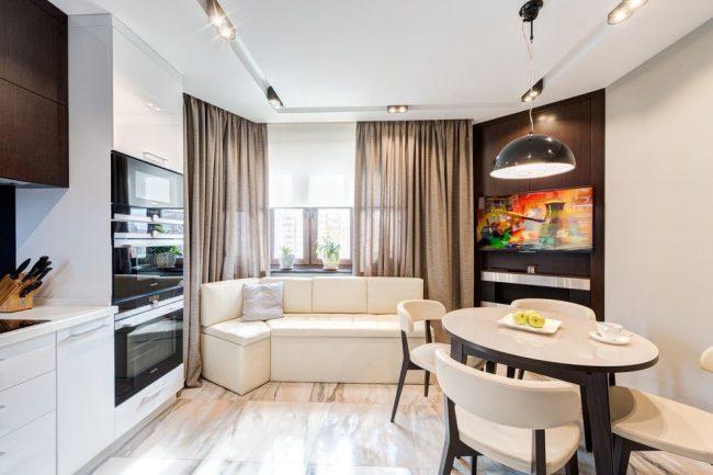 Нестандартный угловой диванчик молочного цвета на современной стильной кухне