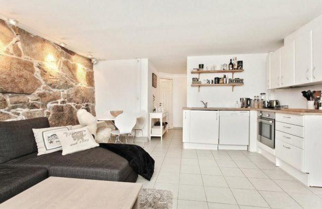 Угловой мягкий диван темно-серого цвета в скандинавском интерьере кухни