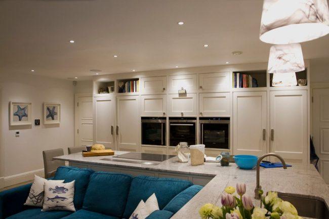 Ярко-бирюзовый угловой диван на светлой кухне
