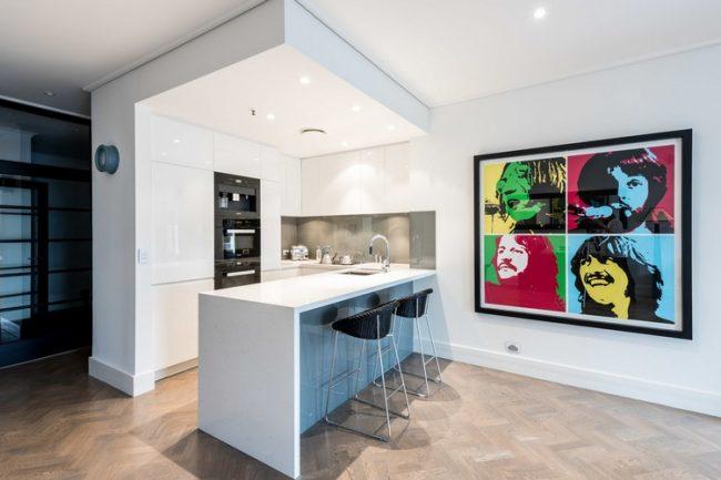 Светлая однотонная кухня разбавлена яркой картиной у барной стойки