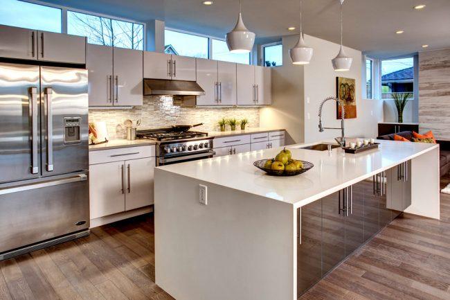 Мелкая декоративная плитка на кухонном фартуке отлично сочетается с глянцевым кухонным гарнитуром