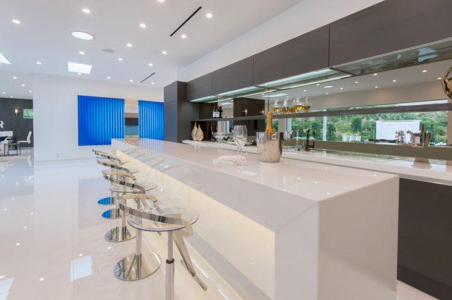 Стильная модерновая кухня в квартире - студии с многоточечным освещением