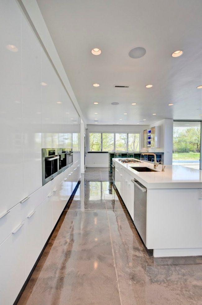 Красивая белая кухня в глянце с каменным полом в теплых тонах