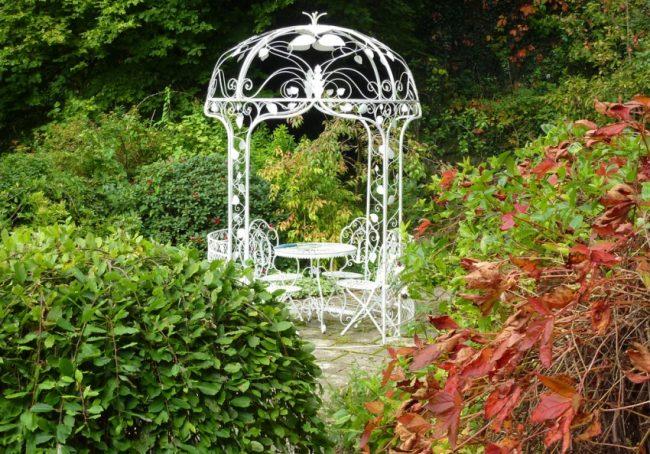 Кованая небольшая беседка для отдыха в саду