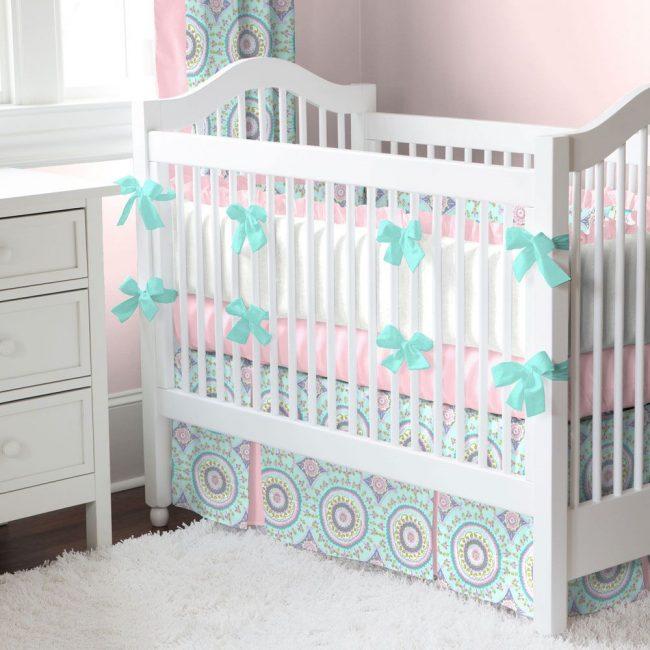 Белые мягкие бортики с розовыми рюшами в белой детской кроватке