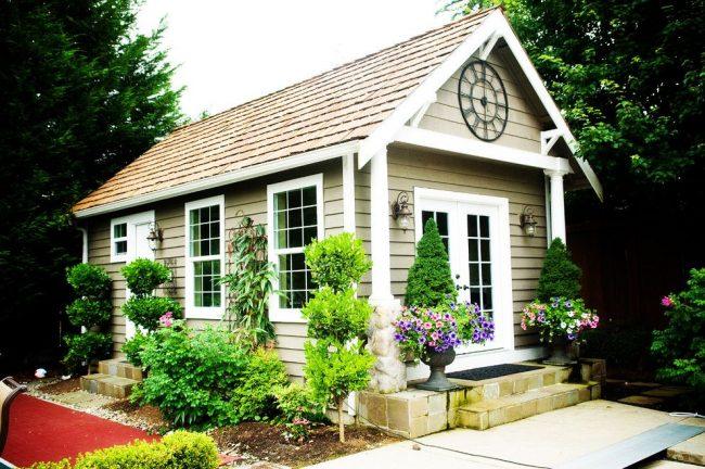 Мини-дом – украшение дачного участка с обилием зелени. Два входа в бытовку, фонари и механические часы под крышей – особенности дома для отдыха