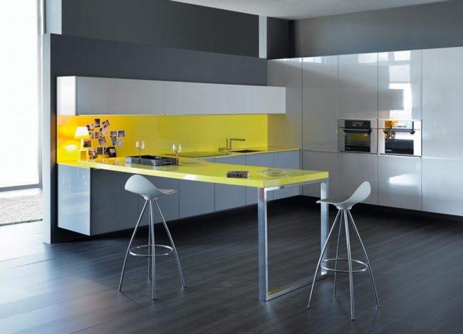 Минималистическая кухня в серо-желтых оттенках: закрытый кухонный гарнитур, барная стойка и встроенная техника