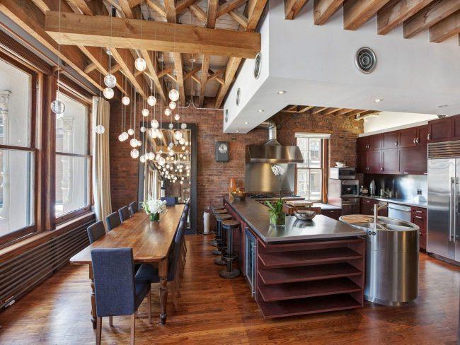 На кухне-гостинной можно удачно использовать барную стойку и обеденную группу, разделив их с помощью освещения