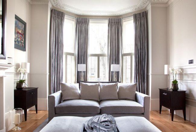 Длинные тяжелые глянцевые шторы в пол, закрепленные под потолком на гибком карнизе, в сочетании с классической потолочной лепниной – ноты шарма в интерьере