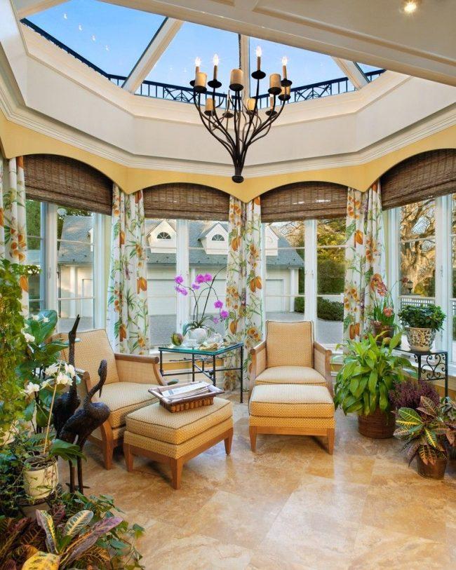 Необычная форма окон с бамбуковыми римскими шторами и текстильными шторами. Оригинальный стеклянный потолок с подвесной массивной металлической люстрой с лампами-свечами