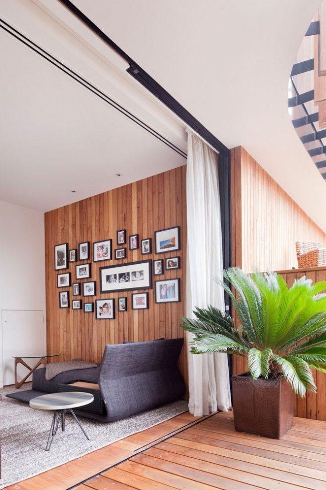 Гибкий карниз для штор: декорирование занавесками дверного проема в гостиной оформленной натуральными материалами