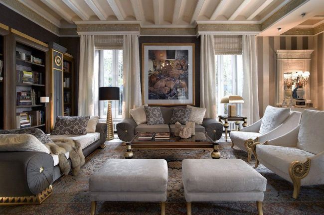 Роскошная гостиная с римскими и обычными шторами на окнах, которые крепятся к стене под потолком, имеющей декорированный потолочный плинтус. Гибкий карниз – правильный выбор для сложного оконного оформления
