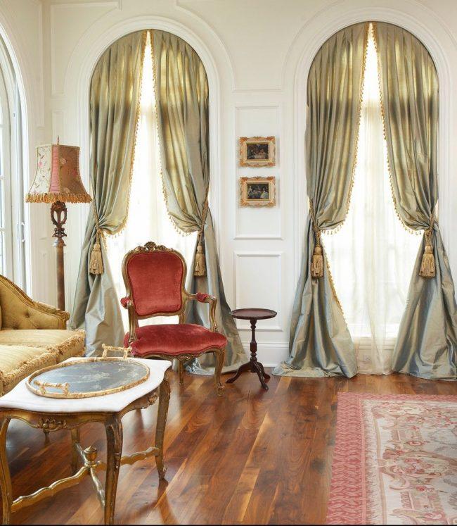 Роскошная гостиная комната в классическом стиле. Гибкий карниз для штор, подвязанных кисточками, на арочном окне – особенность интерьера