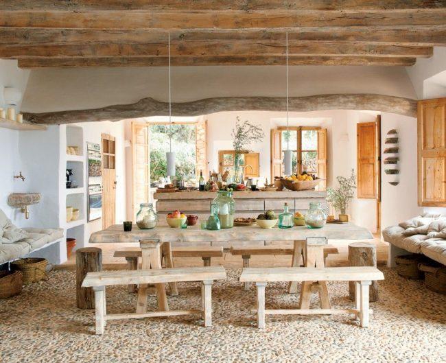 Кухня-гостиная в деревенском доме: пол из камня, деревянная отделка потолка, мебель из натуральных материалов