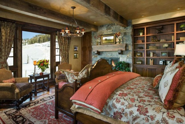 Оформление спальни в загородном доме: каменные стены, ковер на полу, натуральная постель, люстры, картины природы