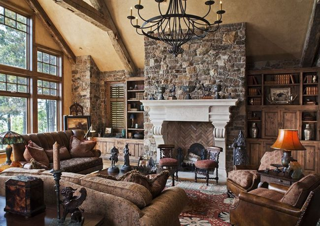 Каменные стены, темные массивные диваны, кованные предметы интерьера в гостиной домика-шале