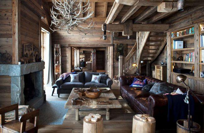 Украшением домика в деревенском стиле станут охотничьи трофеи, деревянные срубы в качестве мебели и отделка камина камнями