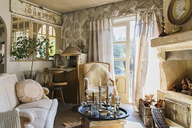 интерьер деревенского дома: уютная гостиная в английском стиле: отделка из натурального камня, светлая мебель, полупрозрачные занавески и камин