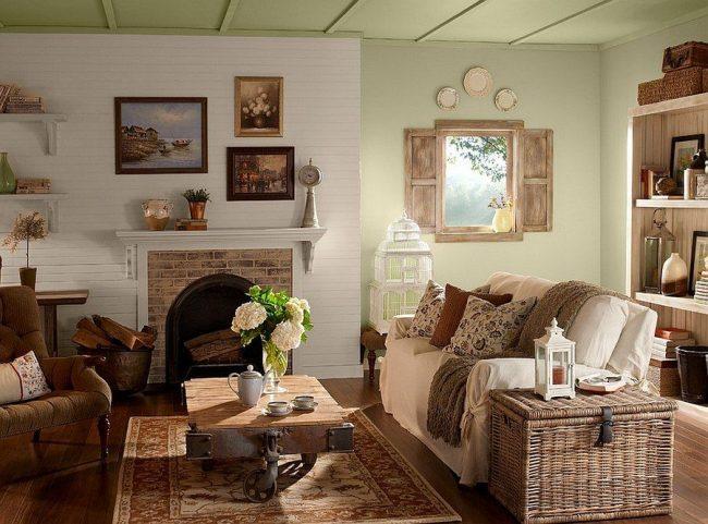 Гостиная в деревенском стиле: деревянная мебель, открытые полки, сундук, камин, живые цветы, окно со ставнями