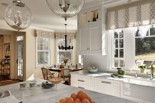 Рабочая кухонная зона в сочетании с укороченными плотными шторами, выполняющими декоративную роль. Обеденная область – укороченные шторы с принтом и функциональные шторы-жалюзи