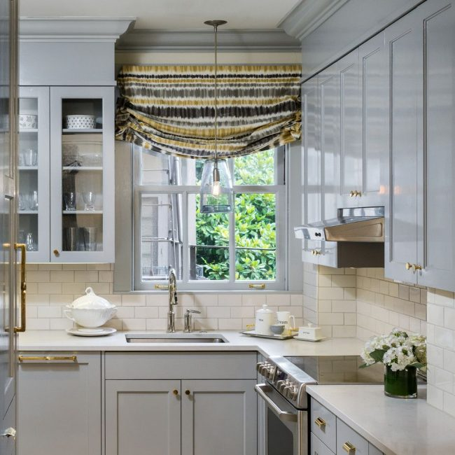 Римские шторы в качестве ярко-выраженного интерьерного элемента в сочетании с однотонным кухонным гарнитуром и общей спокойной цветовой гаммой кухни