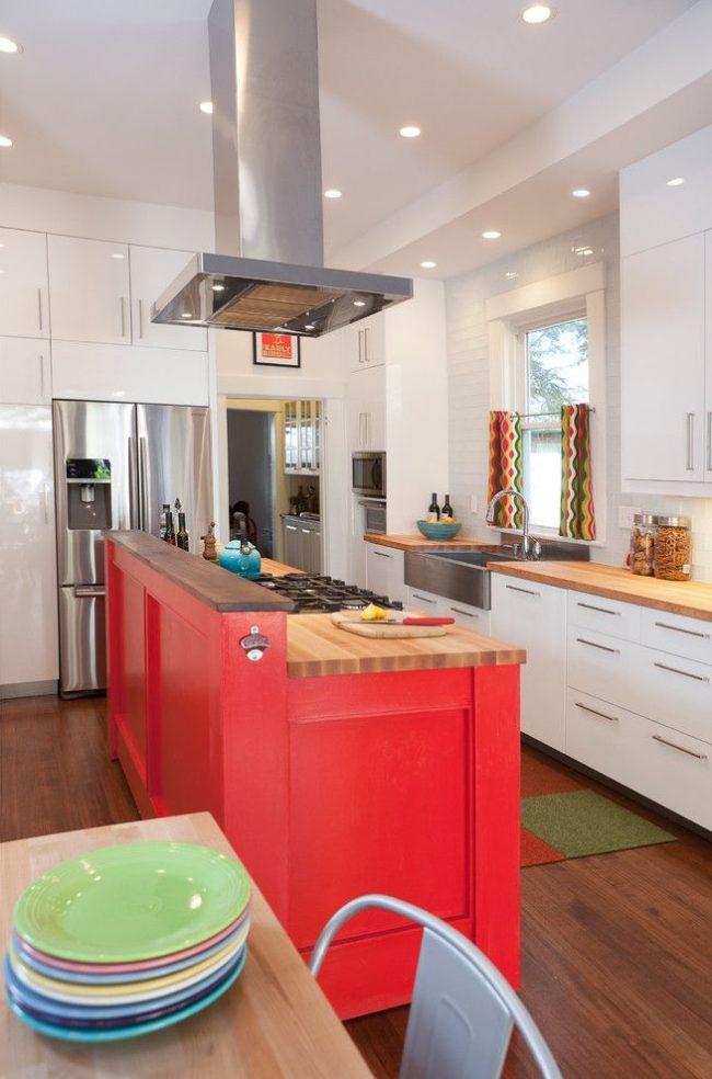 Яркие шторы с геометрическим принтом – акцент на современной кухне, удачно сочетающийся с фасадом кухонного острова насыщенного цвета и разноцветной посудой